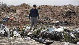 American civil aviation and Boeing investigators search through the debris at the scene of the Ethio