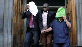 A Kenyan police officer escorts suspects, after fake currency was seized in a personal safety deposi