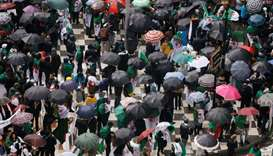 Demonstrators shield themselves from rain under umbrellas as they take part in a protest calling on