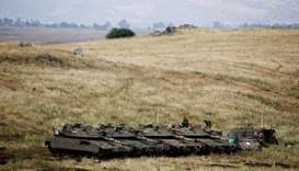 Israeli soldiers stand on tanks near the Israeli side of the border with Syria in the Israeli-occupi