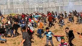 Palestinians flee from tear gas during a protest by the barbed-wire fence with Israel east of Gaza C