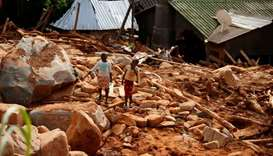 Children carry drinking water yesterday over debris created by Cyclone Idai at Peacock Growth Point