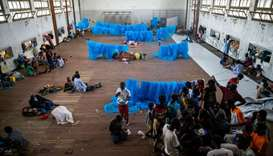 People gather to receive food given to the displaced people in a hall where they are living at the S