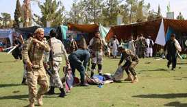 Afghan security personnel carry a injured victims man after following twin explosions in Lashkar Gah