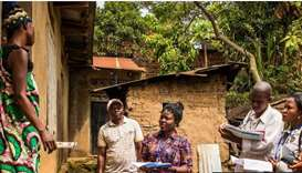 Community representatives visit a family in Beni as part of spreading awareness about Ebola