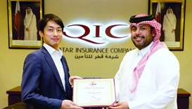 Ahmed al-Jarboey, senior vice president Mena Retail & Motor Claims, awards a certificate of achievem