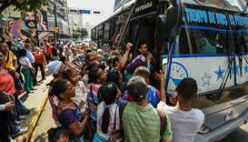 People queue to get on a bus during a partial power cut in Caracas