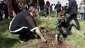 Relatives of the Ethiopian Flight ET 302 plane crash victims plant a memorial tree during a memorial