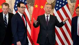 China's Vice Premier Liu He gestures next to US Treasury Secretary Steven Mnuchin and Yi Gang, gover