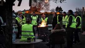 Yellow vest (Gilets jaunes) protestors gather around a fire as they occupy a makeshift camp construc