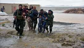 Afghan Security forces carry children after flood affected their homes in Arghandab district of Kand