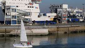 A sailboat glides past the ferry terminal as it leaves the port of Calais, France