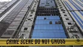 A crime scene ribbon surrounds the burnt building in Dhaka after flames tore through the 22-storey F