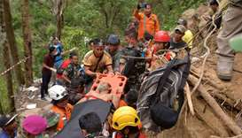 Members of an Indonesian search and rescue team carry a survivor after a mine collapsed in Bolaang M