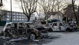 Burnt cars in the street where riots sparked last night, for the third night in a row