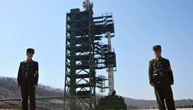 File photo shows two North Korean soldiers standing guard in front of the Unha-3 rocket at at the So