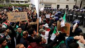 Police members stand guard as people protest against President Abdelaziz Bouteflika, in Algiers, Alg