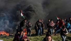 Palestinian protesters holding national flags walk past burning tyres during clashes with Israeli so