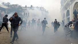 People clash with anti-riot police during the protest against President Abdelaziz Bouteflika, in Alg