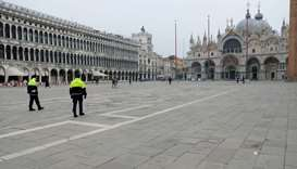 Police officers patrol a virtually deserted St. Mark's Square after a decree orders for the whole of