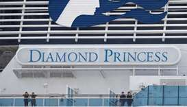 Masked passengers look on from on board the coronavirus-hit Diamond Princess cruise ship docked at Y