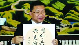 "The ambassador displaying the Chinese saying that reads ""Sailing in the same boat, together we will"