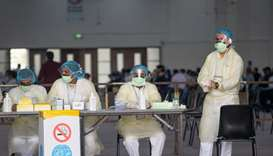Nurses await to admit expatriates in a makeshift coronavirus testing centre at the Mishref Fair Grou