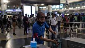 A Delhi Metro Rail Corporation (DMRC) worker cleans automatic fare collection gates at a metro stati