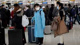 Passengers waiting to check in for an Air China flight are seen with face masks on, after further ca