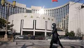 A woman wearing a mask walks past the headquarters of the People's Bank of China, the central bank,