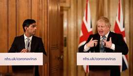 Britain's Chancellor of the Exchequer Rishi Sunak (left) looks on beside Britain's Prime Minister Bo