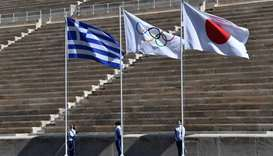 Athletes stand by the Greek, Olympic and Japanese flags during the olympic flame handover ceremony f