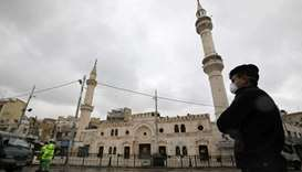 A Jordanian policeman stands guard in front of al Husseini mosque building after closing it to the w