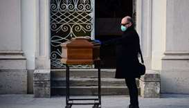 A man touches the coffin of his mother during a funeral service in the closed cemetery of Seriate, n