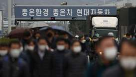 Employees wearing masks to prevent the coronavirus walk at a Hyundai Motors factory in Ulsan, South