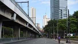 A cyclist passes a nearly empty road in Manila