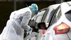 A medical member in protective clothing takes samples at a testing drive-in station for the health a