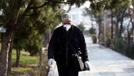 An Iranian man wears a protective mask against the coronavirus as he walks on a street in Tehran, Ir