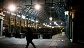 A man walks through a deserted Covent Garden on the day Prime Minister Johnson ordered all pubs and
