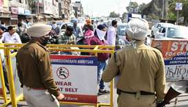 Commuters are stopped by policemen at a checkpoint   following Punjab State government order for a c