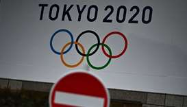 """The Tokyo 2020 logo is pictured next to a """"do not enter"""" street sign in Tokyo"""