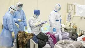 CHECK-UP: Medical staff check a patient's condition at a temporarily converted hospital for coronavi