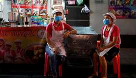 Women wearing masks wait for customers at a food stall during the coronavirus disease (COVID-19) out