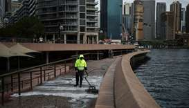 A worker cleans the mostly deserted waterfront area of the Sydney Opera House