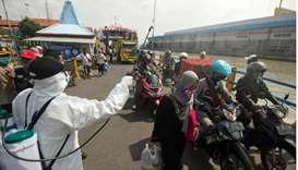 An officer sprays disinfectant on passengers who arrived at a port amid the spread of coronavirus di