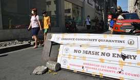 Residents wearing face masks walk past a checkpoint along a street in Manila, yesterday, after the g