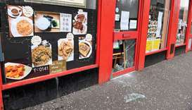 Glass is strewn on the pavement in front of the vandalised door of a Chinese restaurant in Glasgow,