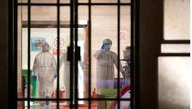 Medical staff in protective suits are seen inside a makeshift hospital that is closed following its