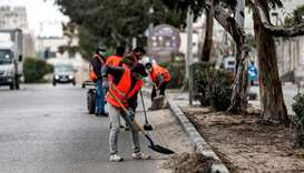 Mask-clad workers clean up a street in Gaza City, yesterday, during lockdown amidst measures to cont