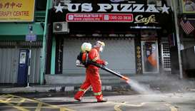 A worker sprays disinfectant on a street during the movement control order due to the outbreak of th